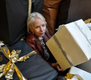 Mehr Zeit statt Zeugs - das symbolisiert das Foto von Gaby Barton unter großen Geschenken begraben.